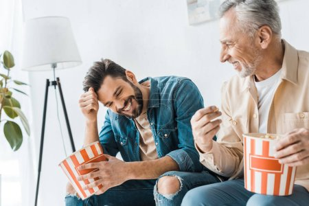 Photo for Happy senior father sitting with smiling son and holding popcorn bucket - Royalty Free Image