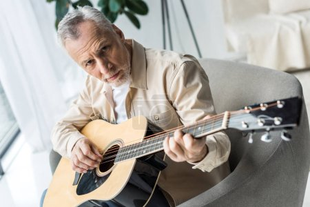 Photo for Senior man playing acoustic guitar and looking at camera - Royalty Free Image