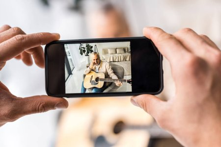 Photo for Cropped view of man taking photo of senior father holding acoustic guitar at home - Royalty Free Image