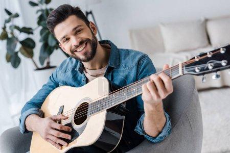 Photo pour Gai homme barbu, jouer de la guitare acoustique à la maison - image libre de droit