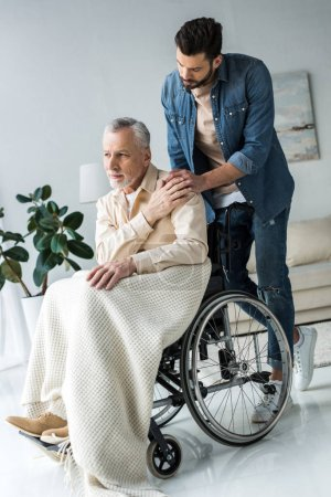 handsome bearded son holding hands with disabled senior father in wheelchair at home