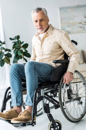 Photo for Disabled senior man sitting in wheelchair at home and looking at camera - Royalty Free Image
