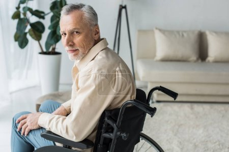 Photo for Disabled retired man sitting in wheelchair at home and looking at camera - Royalty Free Image