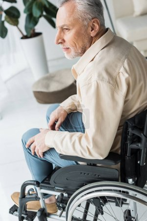 Photo for Disabled retired man sitting in wheelchair at home - Royalty Free Image