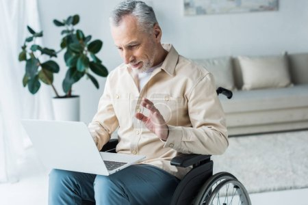 Photo for Cheerful disabled retired man sitting in wheelchair and waving hand while having video call - Royalty Free Image