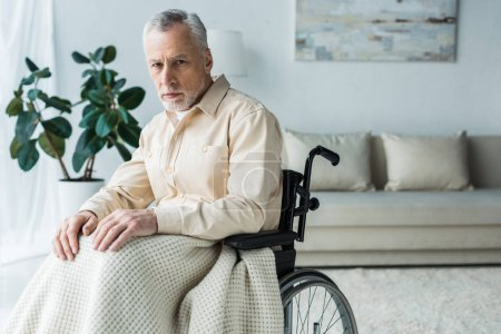 Photo for Sad disabled retired man sitting in wheelchair and looking at camera - Royalty Free Image