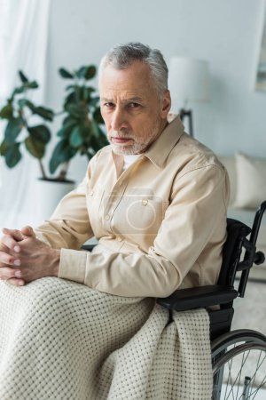 Photo for Sad disabled retired man sitting in wheelchair with clenched hands and looking at camera - Royalty Free Image