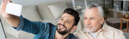 Photo pour Plan panoramique de fils barbu heureux prenant selfie avec père gai à la maison à la retraite - image libre de droit