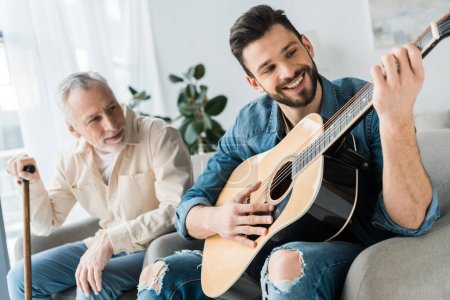 Photo for Cheerful bearded man playing acoustic guitar near senior father at home - Royalty Free Image