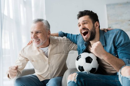Photo for Happy retired man watching championship and cheering with handsome son holding football - Royalty Free Image