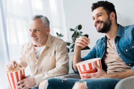Foto de Padre jubilado feliz sentada con hijo y sosteniendo el cubo de las palomitas mientras vemos la tele - Imagen libre de derechos