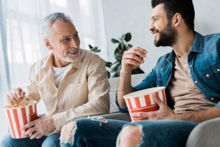 Photo pour Heureux père retraité regardant son fils et tenant seau de maïs soufflé à la maison - image libre de droit