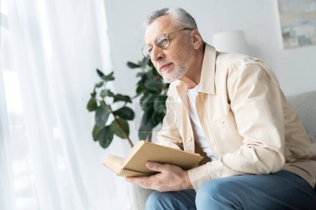Photo for Senior man in glasses holding book while sitting at home - Royalty Free Image