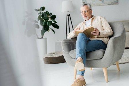 Foto de Pensativo hombre mayor en gafas sosteniendo libro mientras está sentado en sillón en casa - Imagen libre de derechos