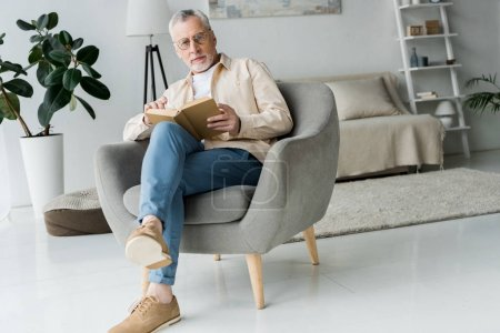 pensive retired man in glasses holding book while sitting in armchair at home