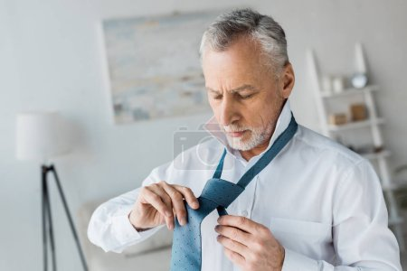 Photo for Confident and elegant retired man tying blue tie at home - Royalty Free Image