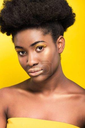Foto de Atractiva mujer afroamericana con maquillaje de moda mirando a la cámara aislada en amarillo - Imagen libre de derechos