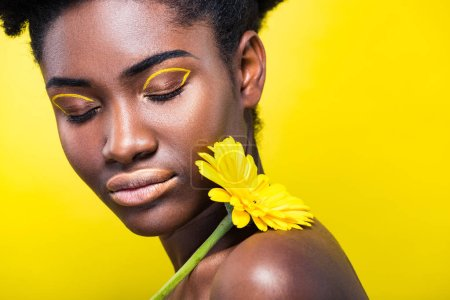Photo for Cropped view of african american girl with closed eyes holding flower isolated on yellow - Royalty Free Image