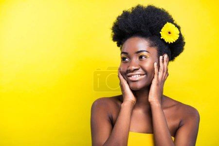Photo pour Gai souriant femme afro-américaine avec la fleur sur le jaune - image libre de droit
