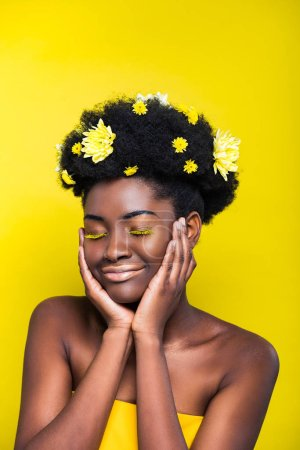 Relaxed african american girl with chrysanthemums in hair with closed eyes isolated on yellow