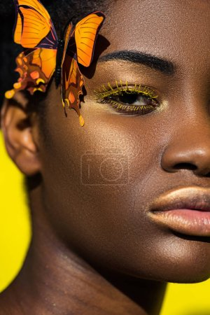 Photo for Cropped view of african american girl with butterfly looking at camera on yellow - Royalty Free Image