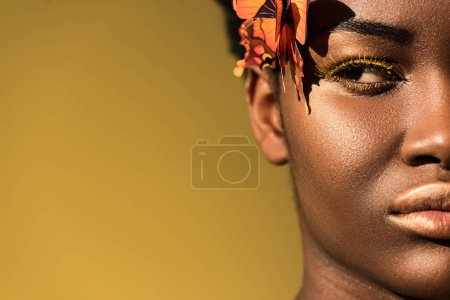 Photo for Cropped view of serious african american woman with butterflies looking away on brown - Royalty Free Image