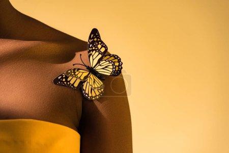 Photo pour Vue recadrée de la femme afro-américaine avec papillon sur l'épaule sur orange - image libre de droit
