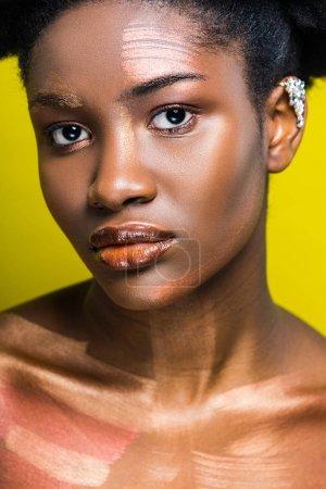 Foto de Pensive atractiva mujer afroamericana con puño de oreja en amarillo - Imagen libre de derechos
