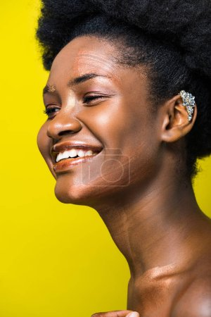 Photo for Laughing african american girl with ear cuff isolated on yellow - Royalty Free Image