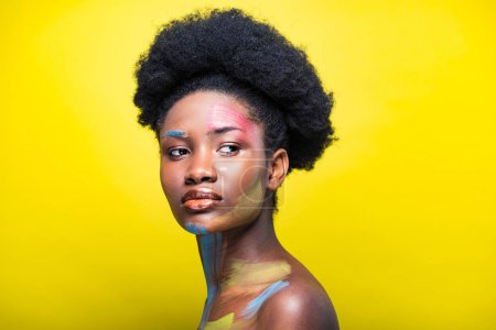 Photo for Pensive african american woman with colorful body art on yellow - Royalty Free Image