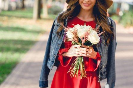 Photo pour Vue recadrée de femme heureuse tenant des fleurs tout en se tenant dans le parc - image libre de droit
