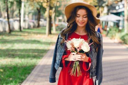 Photo pour Attrayant fille en chapeau regardant des fleurs tout en se tenant dans le parc - image libre de droit
