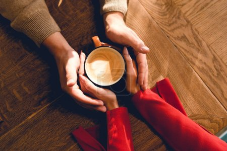 Photo for Top view of man and woman holding cup of coffee in cafe - Royalty Free Image