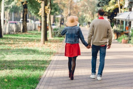 Photo for Back view of man and woman in hat holding hands while walking in park - Royalty Free Image