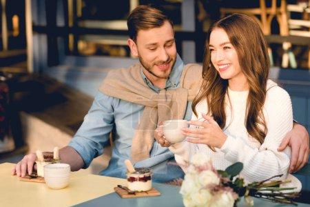 Photo pour Homme gai regardant la cuvette dans les mains de la petite amie heureuse dans le café - image libre de droit