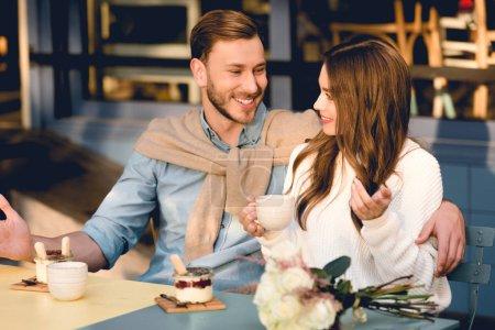 Photo pour Homme gai regardant la petite amie heureuse retenant la cuvette de café - image libre de droit