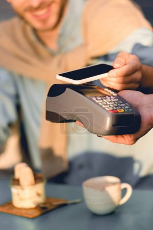 Photo for Cropped view of man paying with smartphone in cafe - Royalty Free Image