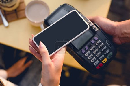 Photo for Cropped view of young woman paying with smartphone in cafe - Royalty Free Image