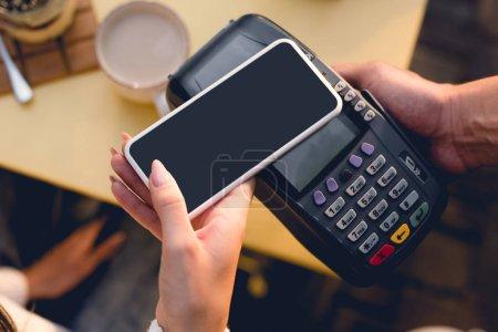 Photo pour Vue recadrée de jeune femme payant avec le smartphone dans le café - image libre de droit