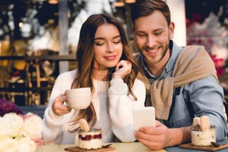 Photo pour Homme gai regardant le smartphone près de la fille heureuse retenant la cuvette de café - image libre de droit