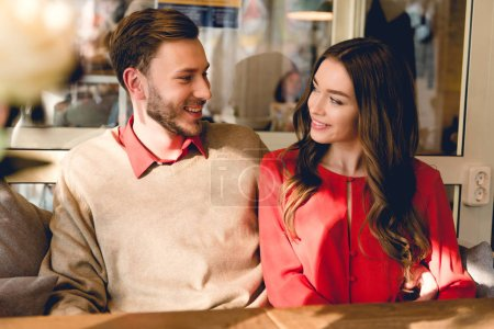 Photo for Happy man and young woman looking at each other in cafe - Royalty Free Image