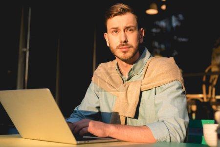 Photo pour Beau pigiste barbu en utilisant un ordinateur portable tout en travaillant dans un café - image libre de droit