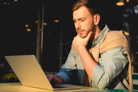 Photo for Pensive bearded freelancer using laptop while working in cafe - Royalty Free Image