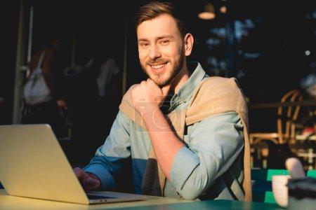 Photo pour Joyeux pigiste barbu assis près d'un ordinateur portable et regardant la caméra - image libre de droit