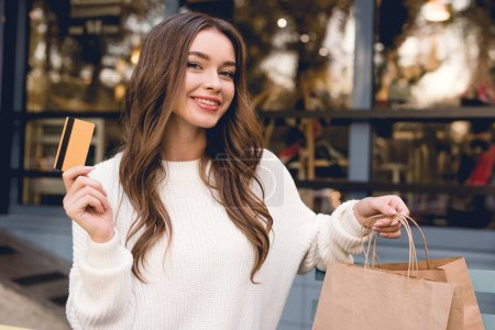 Photo for Cheerful girl holding credit card and shopping bags - Royalty Free Image