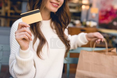 Photo for Cropped view of happy girl holding credit card and shopping bags - Royalty Free Image
