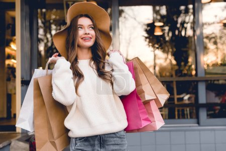 Photo for Happy young woman in hat smiling while holding shopping bags - Royalty Free Image