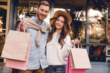Photo pour Gai barbu homme et femme dans chapeau tenant des sacs à provisions - image libre de droit