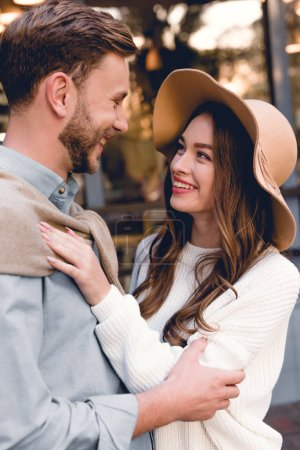 Photo for Cheerful young woman in hat looking and hugging happy boyfriend - Royalty Free Image