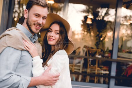 cheerful young woman in hat hugging handsome and happy boyfriend